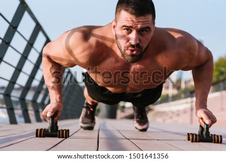 Shirtless muscular young man doing push ups by the river