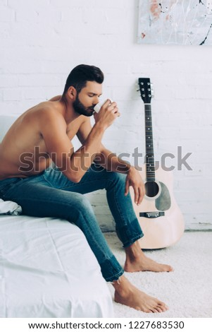 shirtless muscular young man in jeans drinking coffee cup during morning time in bedroom at home