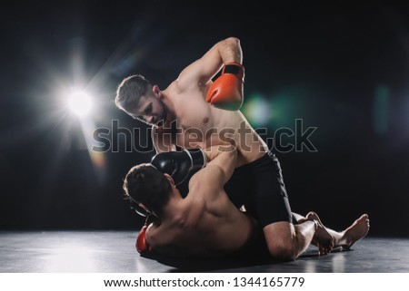 shirtless strong mma fighter in boxing gloves punching opponent in head while sportsman lying on floor