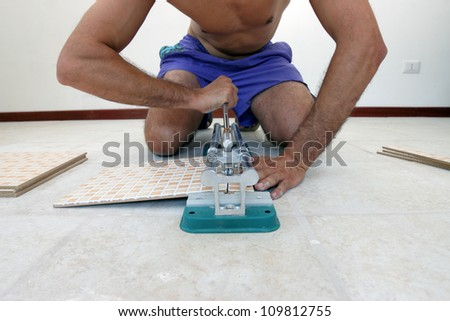shirtless worker with tiling tool, cutting tiles close up