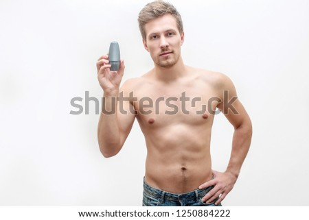 Shirtless young man hold deodorant in hand. He shows it. Guy look straight. He pose. Isolated on white background.