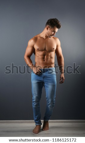 Shirtless young man in stylish jeans near grey wall