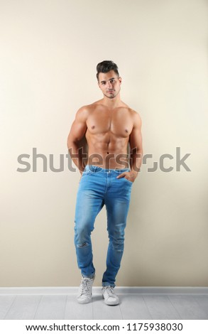 Shirtless young man in stylish jeans near light wall