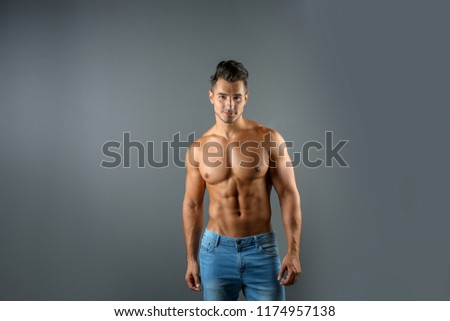 Shirtless young man in stylish jeans on grey background