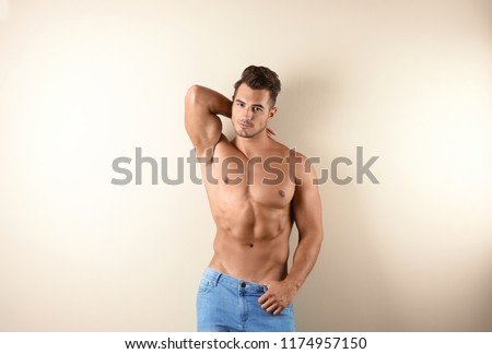 Shirtless young man in stylish jeans on light background