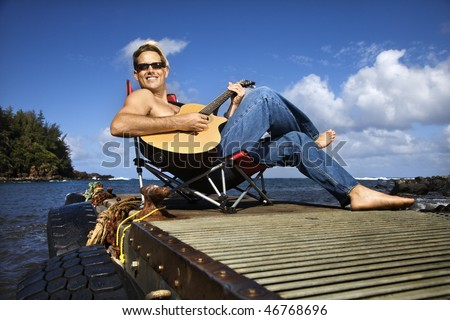 Shirtless young man wearing sunglasses, sitting on a pier and playing a guitar and smiling. Horizontal shot.