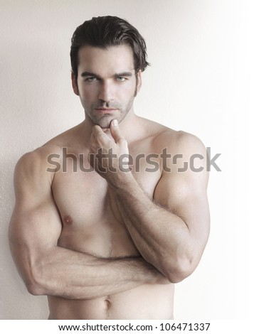 Shirtless young man with hand to chin against neutral background