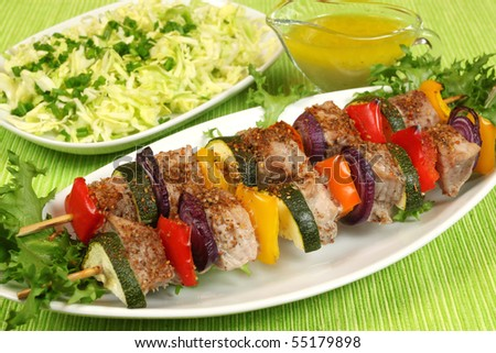 Shish kebab - delicious meat cuisine with  zucchini, onions and peppers. Salad in background.