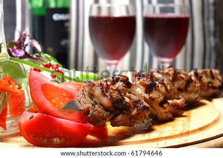 Shish kebab on a wooden support with vegetables and spices