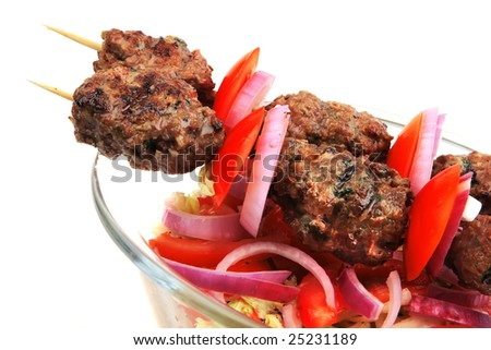 shish kebab with salad over white background