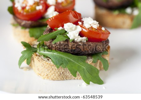 Shitake mushroom tapas with cherry tomatoes and crumbled  feta cheese. - stock photo