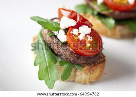 Shitake mushroom tapas with cherry tomatoes and crumbled  feta cheese.