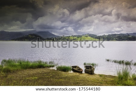 Shllong, Meghalaya, India: Two wooden boats moored on Umiam Lake as a monsoon storm threatens over the Khasi Hills near Shillong, Meghalaya, India.