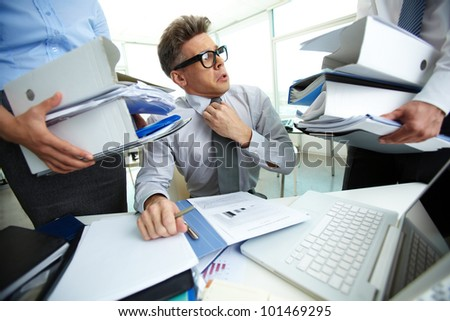 Shocked accountant looking at huge piles of documents held by his partners