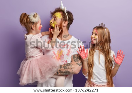 Shocked affectionate dad has dirty face from paints, opens mouth widely, holds little daughter on hands. Smiling girl wears crown, shows palms in pink watercolors. Joyful father and children have fun #1376242271