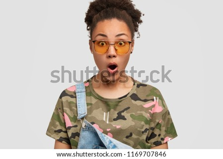 Stock Photo Shocked African American girl opens mouth, stares with surprised expression, wears trendy shades, dressed in fashionable clothes, feels startled, looks in great disbelief, isolated on white wall