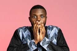 Shocked african american guy in traditional costume covering his mouth with hands, pink studio background. Closeup of astonished black man in african costume, seeing something breathtaking