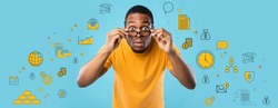 Shocked African American guy looking at camera through glasses, expressing surprise on blue studio background, collage with business, money and finance pictograms. Financial literacy concept. Panorama