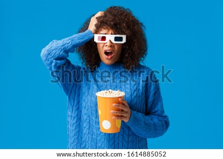 Shocked african-american pretty woman concerned with shocking cliffhanger in movie, grab head uneasy and upset, drop jaw, holding popcorn watching film in cinema, blue background