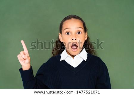 shocked african american schoolgirl showing idea gesture while standing near green chalkboard #1477521071