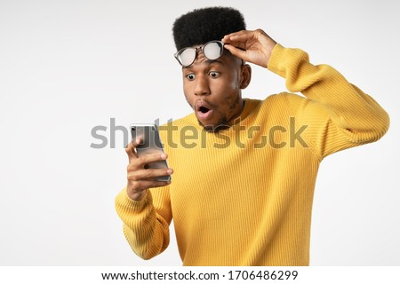 Shocked african man while watching in smartphone on isolated white background