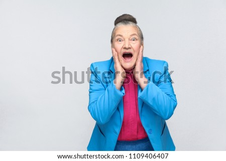 shocked aged woman. Emotion and feelings, Portrait of handsome expressive grandmother with light blue suit and pink shirt standing with collected gray hair. Studio shot, isolated on gray background #1109406407