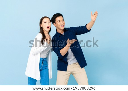 Shocked amazed Asian couple pointing hands up to empty space above on isolated light blue background