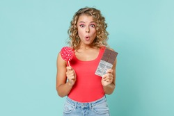 Shocked amazed surprised young blonde woman wearing pink basic casual tank top standing hold chocolate bar round lollipop looking camera isolated on blue turquoise colour background studio portrait