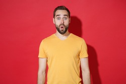 Shocked amazed young bearded man guy in casual yellow t-shirt posing isolated on red wall background studio portrait. People sincere emotions lifestyle concept. Mock up copy space. Keeping mouth open