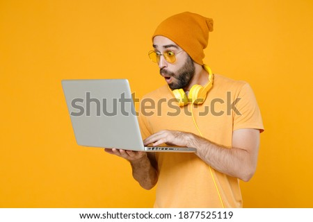 Shocked amazed young bearded man 20s wearing basic casual t-shirt headphones eyeglasses hat standing hold working on laptop pc computer isolated on bright yellow colour background, studio portrait