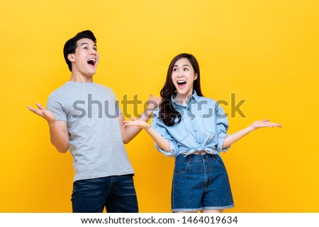 Shocked amazed young man and woman with open palms and mouth against yellow studio background