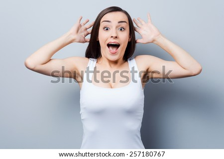 Shocked and happy. Surprised young woman staring at camera while standing against grey background