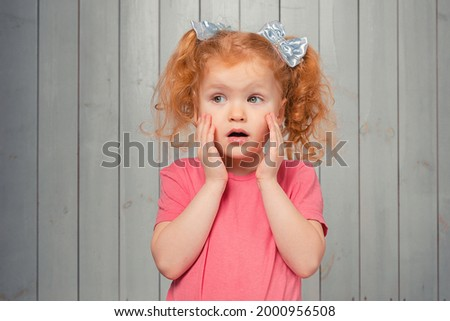 Shocked and scared redhead little girl 4-6 years old, staring startled at left and frightened, afraid of something scary. Studio shot, light wooden background Stockfoto ©