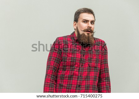 Shocked and surprised bearded man. Expressive facial expressions. Studio shot, gray background #715400275