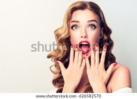 Shocked and surprised girl screaming covering  mouth her hands . Curly hair woman amazed .Beautiful girl  with curly hair and red nails manicure. Presenting your product..Expressive facial expressions