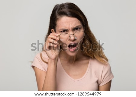 Shocked angry young woman in disbelief lowering glasses looking at camera with indignation isolated on grey blank studio background, confused girl frowning touching eyeglasses feeling flabbergasted Stock foto ©