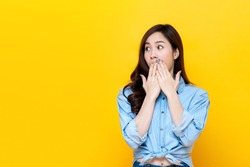 Shocked asian woman covering mouth with hands isolated on bright yellow studio background