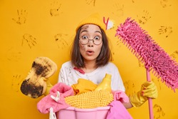 Shocked Asian woman poses with dirty sponge and mop busy doing work about house cleans everything wears round spectacles hat t shirt rubber gloves has cleaning day isolated on untidy yellow wall
