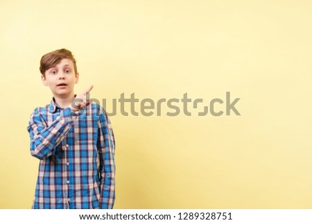shocked astonished amazed boy points with index finger at empty space, advertisement or product placement, banner or poster template, surprise and amazement, emotion facial expression