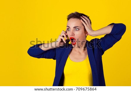 Shocked at phone Half length body woman short hair girl boy alike trans-gender talking on cell phone mobile looking stunned frustration amazement on face stress hand on head isolated yellow background - Shutterstock ID 709675864