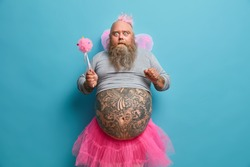 Shocked bearded male princess wears wings and crown holds magic wand has big tattooed belly prepares for carnival stares bugged eyes. Stunned man in princess costume poses indoor plays with daughter