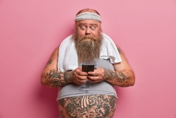 Shocked bearded man in sport outfit, takes break after physical exercises at home, holds smart phone, burns calories and fat, downloads application, poses against rosy wall. Thick fat guy with gadget