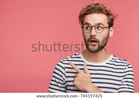 Shocked bearded young man with trendy hairdo and mustache points at copy space as poses against pink background, advertises something or being surprised to see high prices. It`s unbelievable! #744197425