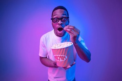 Shocked black guy in 3D glasses eating popcorn in cinema under neon light, funny surprised african american man watching interesting movie and looking at camera with excitement over studio background
