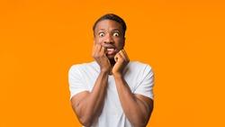 Shocked Black Man Looking At Camera Touching Face Posing On Orange Studio Background. Panorama, Empty Space