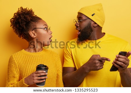 Shocked black woman and man impressed while scroll social media page. Emotioanl lady with crisp hair hears shocking newsfrom friend who indicates at cell phone screen, holds paper cup of beverage #1335295523
