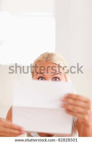 Shocked blond woman reading a letter in her living room