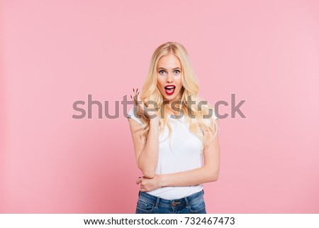 Shocked blonde woman looking at the camera with open mouth over pink background