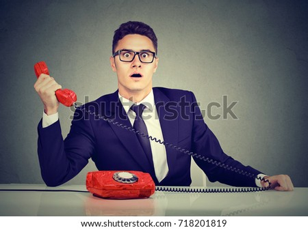 Shocked business man receiving bad news on the phone