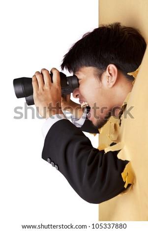 Shocked businessman breaking through a paper wall looking through binoculars